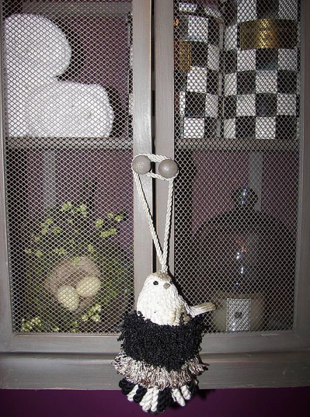 [Image: Black and white handmade tassel with bird figurine. ]