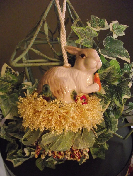 [Image: Beautiful handmade tassel with a bunny figurine in colors green and yellow, hanging from a fake plant stand. ]