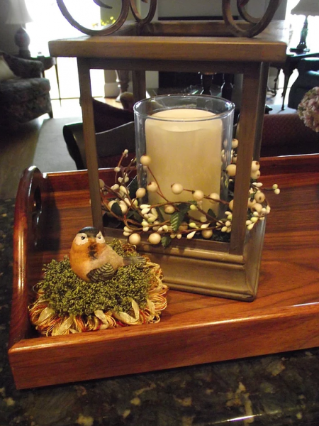 [Image: Cute bird figurine tassel in the color green with yellow and red accents sitting beside a candle holder. ]