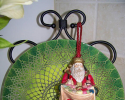 Festive Christmas tassel with a Santa Clause figurine in colors red, gold and green.